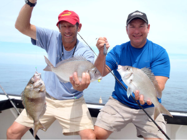 "Rich Lazar with a double, while Captain Tom Mikoleski shows off a big ""pork chop"" porgy."
