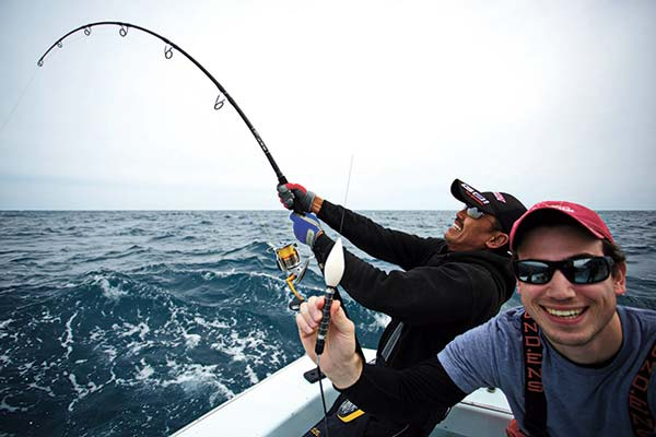 Ng Yam Pin (left) traveled all the way from Malaysia to North Carolina's Outer Banks to tangle with his first Atlantic bluefin tuna, a 76-inch fish that he bested in 37 minutes before it was tagged by the author (right).