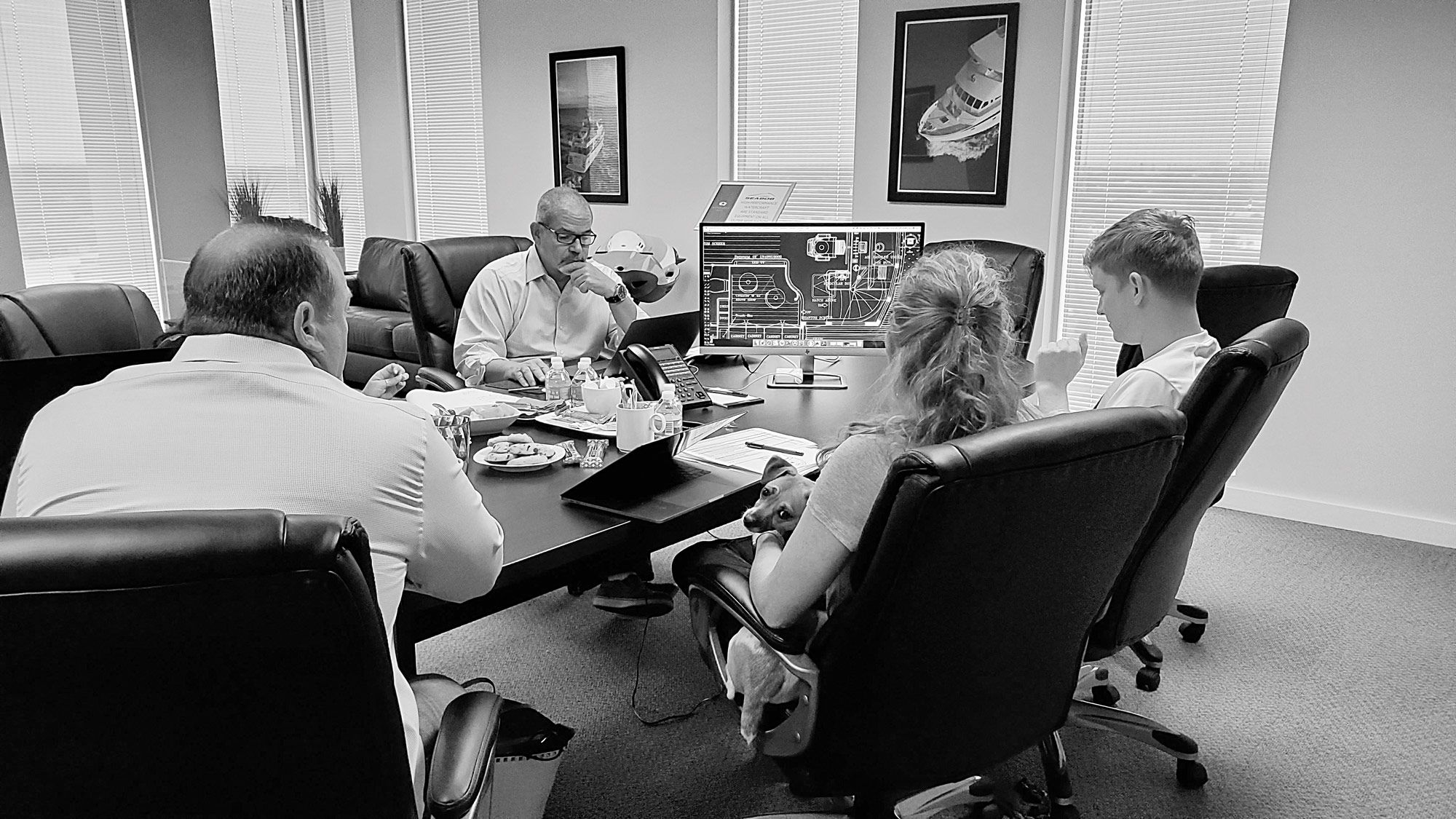 Owners of the Outer Reef 610 <i>Equiessence</i> (and their dog) in a design session with company president Jeff Druek for their second Outer Reef, a 720 Deluxbridge Motoryacht.