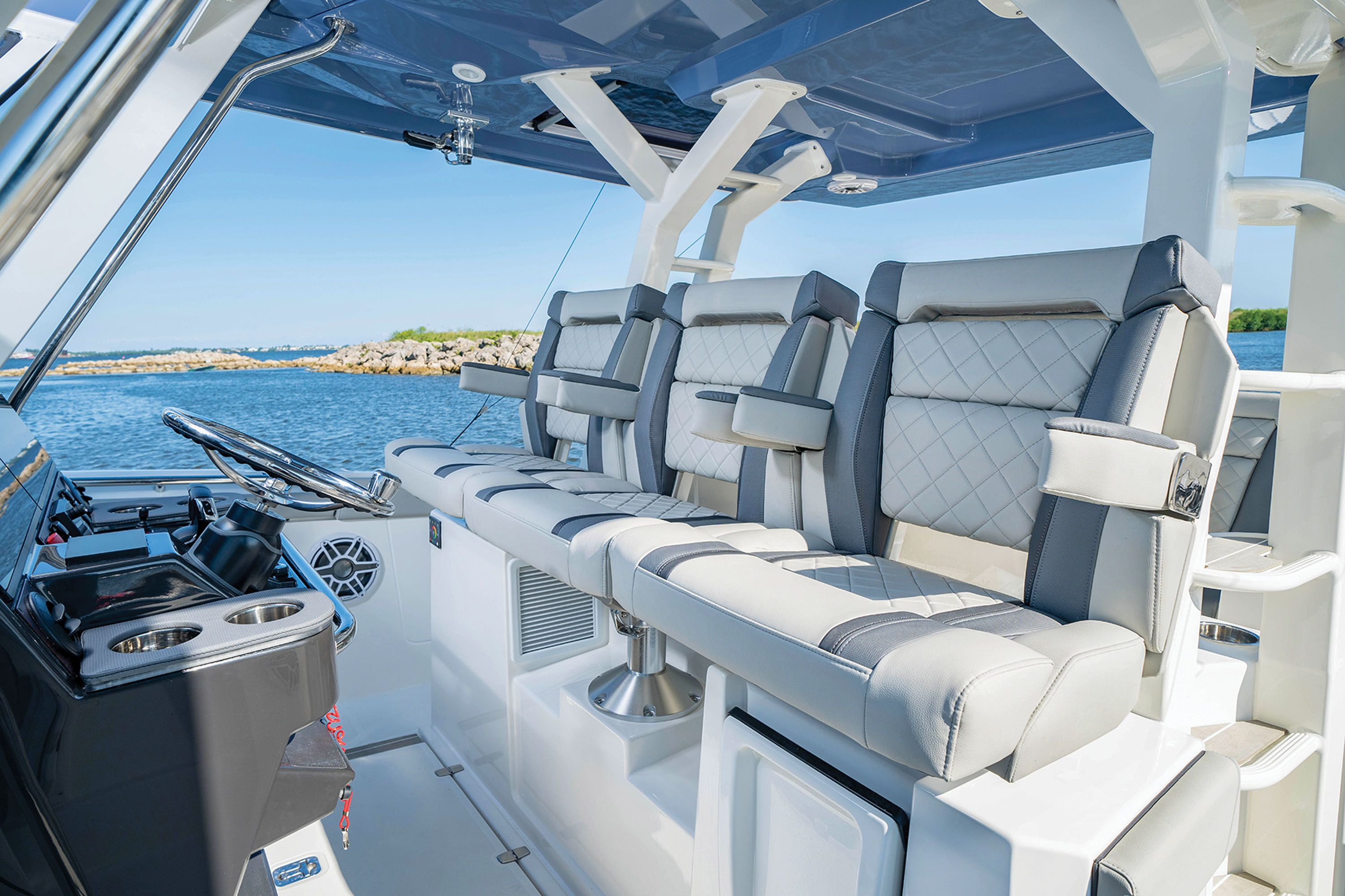 Captain's chairs with folding armrests and flip-up bolsters sit three at the helm.